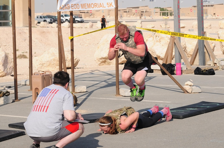 Military members worked hard to complete sets of burpees at Al Udeid Air Force Base Nov. 21. After each couplet there were 16 lateral partner over burpees. The number 16 represents 16 point hits which are automatic failures for EOD technicians in school. (U.S Air Force photo courtesy of Senior Master Sgt. Stephan Kovacs)