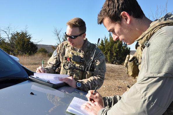 Instructor Staff Sgt. Steven Smith helps Senior Airman Phil Schneider, a student Joint Terminal Attack Controller, prepare coordinates to call in a simulated air strike during the class's field training exercise south of Warsaw, Missouri on November 19. Academic portions of the class rely on JTACs playing the role of pilots in hypothetical missions, but the exercise gives students the opportunity to speak with experienced pilots from the 442d Fighter Wing over the radio in realistic scenarios. Warsaw has hosted the exercises since 1993. (U.S. Air Force photo/ Technical Sgt. Emily F. Alley)