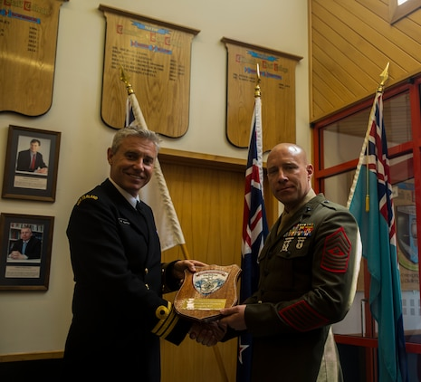 U.S. Marine Corps Sgt. Maj. Christian L. Charkowski, right, presents a plaque to New Zealand Defence Force Commander Nigel Philpott at the Defence Force Command and Staff College, Wellington, New Zealand, Nov. 19, 2015. Charkowski is the first U.S. Marine and second U.S. service member to graduate from the college. He attended the Joint Warrant Officers' Advanced Course, where the objectives were to prepare senior level leaders for senior strategic advisory positions, increase the students' knowledge of regional security for the Southwest Pacific and provide the students with insight into the workings of the government. Charkowski, from Madison, Wisconsin, is the battalion sergeant major for 3rd Combat Assault Battalion, 3rd Marine Division, III Marine Expeditionary Force. Philpot, from Wellington, New Zealand, is the commandant of the Defence Force Command and Staff College. (Marine Corps. photo by Cpl. Tyler S. Giguere/Released)