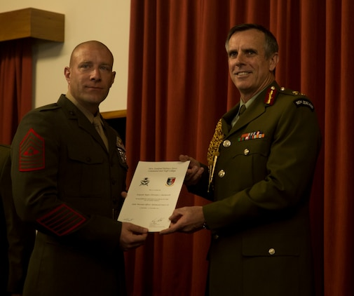 U.S. Marine Corps Sgt. Maj. Christian L. Charkowski, left, receives his graduation certificate from New Zealand Defence Force Lt. Gen. Tim Keating, at the Defence Force Command and Staff College, Wellington, New Zealand, Nov. 19, 2015. Charkowski is the first U.S. Marine and second U.S. service member to graduate from the college. He attended the Joint Warrant Officers' Advanced Course there, where the objectives were to prepare senior level leaders for senior strategic advisory positions, increase the students' knowledge of regional security for the South West Pacific and provide insight into the workings of the government. Charkowski, from Madison, Wisconsin, is the battalion sergeant major for 3rd Combat Assault Battalion, 3rd Marine Division, III Marine Expeditionary Force. Keating is the Chief of Defence for the New Zealand Defence Force. (Marine Corps. photo by Cpl. Tyler S. Giguere/Released)