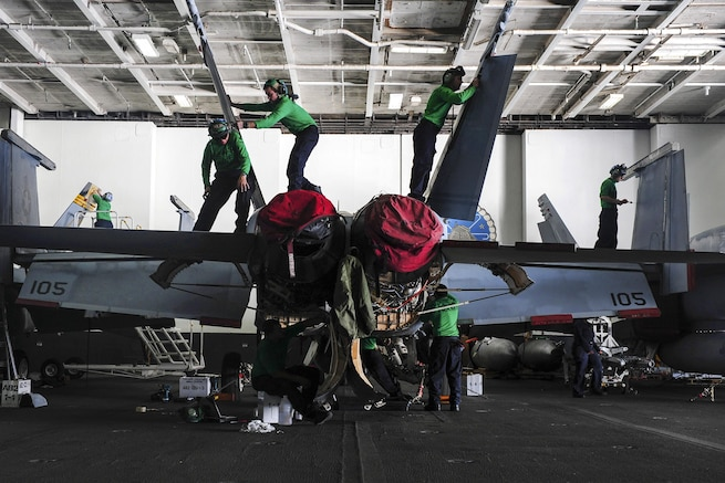 U.S. sailors perform maintenance on an F/A-18F Super Hornet in the hangar bay of the aircraft carrier USS Dwight D. Eisenhower in the Atlantic Ocean, Nov. 28, 2015. The sailors are assigned to Strike Fighter Squadron 32. U.S. Navy photo by Petty Officer 3rd Class Taylor L. Jackson