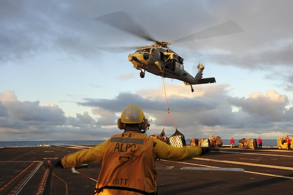 Navy Petty Officer 1st Class Manuel Arias directs an MH-60S Sea Hawk helicopter to lower its cargo onto the flight deck of the aircraft carrier USS Dwight D. Eisenhower during a replenishment at sea with the USNS Kanawha in the Atlantic Ocean, Nov. 29, 2015. Arias is an aviation boatswain's mate. U.S. Navy photo by Petty Officer 3rd Class Taylor L. Jackson