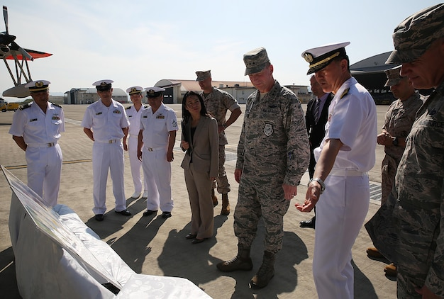 U.S. Air Force Lt. Gen. John L. Dolan, commander of U.S. Forces Japan and 5th Air Force, center, and Rear Adm. Naoki Sonoda, commander of Japan Maritime Self-Defense Force, Fleet Air Wing 31, right, view memorabilia from Dolan's air rescue mission at the Japan Maritime Self-Defense Force hangar, Marine Corps Air Station Iwakuni, Japan, Sept. 29, 2015. During a brief stop at the installation, Dolan took time to visit the JMSDF members who rescued him after an aircraft collision, forcing Dolan to eject from his F-16, 630 nautical miles away from Tokyo into the Pacific Ocean. Almost two decades later, Dolan and his saviors reconnected.