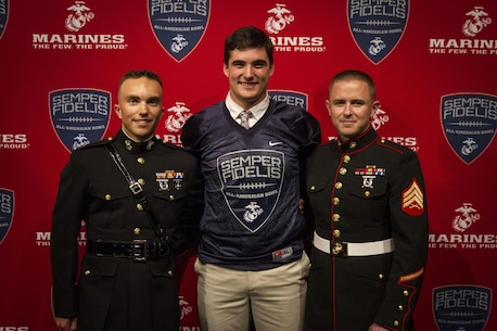 Danny Dalton, a tight end football player for Marshfield High School in Marshfield, Massachusetts, stands with Capt. Zachary Johnson and Sgt. Cody Lee after receiving his Semper Fidelis All-American Bowl jersey at the school, Sept. 30. Following his selection at a previous football camp, Dalton has been chosen to play in the SFAAB game this January in California. Dalton has graduated from Marshfield recently and has committed to Penn State University and their football team. Johnson is the executive officer of Recruiting Station Portsmouth, New Hampshire, and Lee is a canvassing recruiter with Recruiting Substation Brockton, Mass.