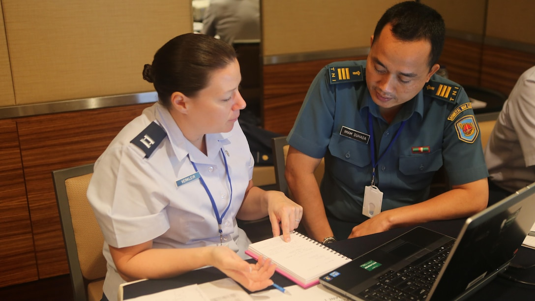 U.S. Air Force Capt. Jodi Verkleir, 36th Medical Support Squadron Readiness Flight commander, discusses a simulated earthquake scenario with Indonesian Capt. Imam Suhada, a medical planner, during Exercise Gema Bhakti in Jakarta, Indonesia, Sept. 16, 2015. Verkleir joined more than 40 U.S. Pacific Command participants during the 10-day bilateral joint exercise designed to promote positive military relations, increase cultural awareness and enhance training and understanding of respective capabilities. U.S. Air Force photo by Matt Lyman
