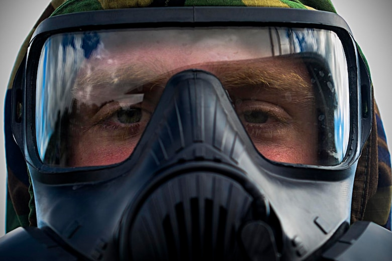 Airman 1st Class Rand McCrady, 36th Munitions Squadron munitions system journeyman, wears an M-50 mask during chemical, biological, radiological and nuclear training Oct. 1, 2015, at Andersen Air Force Base, Guam. Emergency managers teach a CBRN refresher course once a month to Airmen who are preparing for a permanent change of station or deploying to medium or high-threat level duty stations. (U.S. Air Force photo by Senior Airman Joshua Smoot/Released)