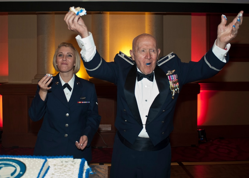 Retired Col. George Peterson and Airman Brenna Albright celebrate after cutting and eating the 2015 Las Vegas Air Force Ball cake during the ceremony at the South Point Hotel and Casino in Las Vegas, Sept. 26, 2015. It is tradition for the oldest and youngest Airmen in attendance to make the cake's ceremonial first cut. (U.S. Air Force photo by Staff Sgt. Siuta B. Ika)