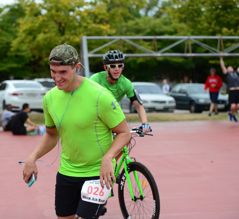 A runner takes off as his team member cycles in during a dual component race held as part of the second annual Osan Cup held at Osan Air Base, Republic of Korea, Sept. 30, 2015. Competing either alone or as a member of a team the participants contributed to their squadrons overall standing during the two-day event. (U.S. Air Force photo/Staff Sgt. Amber Grimm)