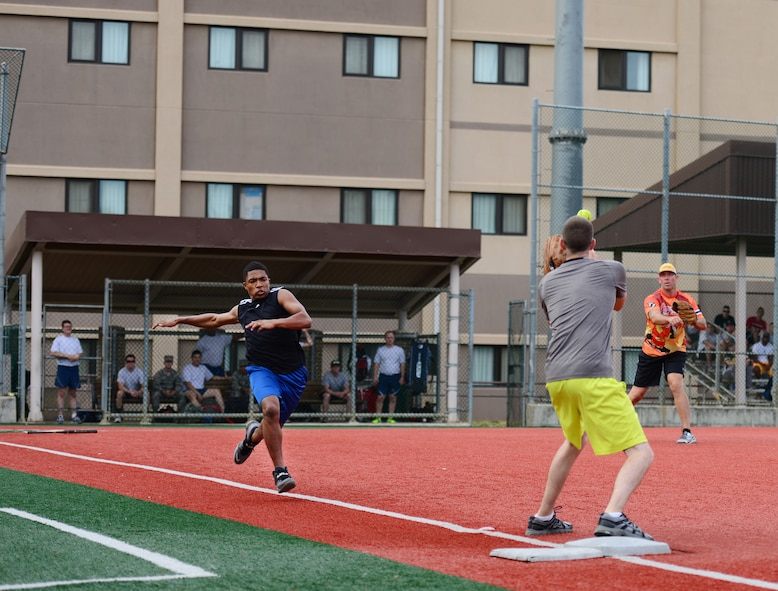 Staff Sgt. Justin McCallus, 51st Aircraft Maintenance Squadron, scores an out against an Airman from the 51st Logistic Readiness Squadron as the two teams compete at Osan Air Base, Republic of Korea, Sept. 29, 2015. Softball was just one of the 19 different events that made up the second annual Osan Cup. (U.S. Air Force photo/Staff Sgt. Amber Grimm)