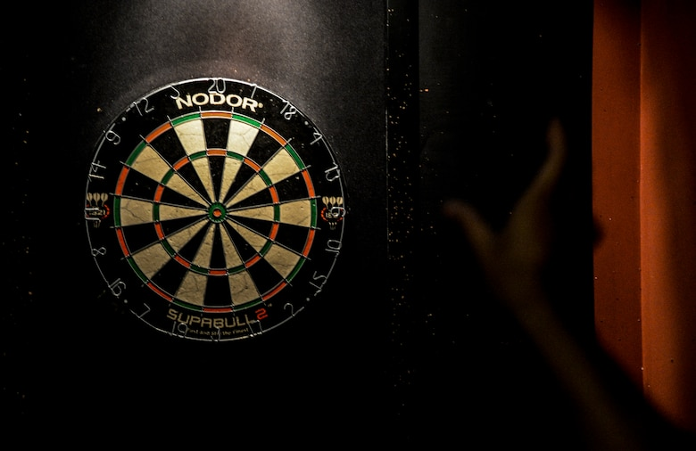 An Airman throws a dart during a dart tournament at the Enlisted Club as part of the Osan Cup at Osan Air Base, Republic of Korea, Sept. 30, 2015. The Osan cup is a sport-oriented, two-day event that puts squadrons and service members against each other in a battle royal to show who has the most skill, strength and knowledge. (U.S. Air Force photo/Tech. Sgt. Travis Edwards)