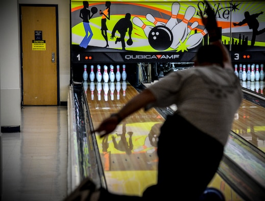 Senior Airman William McDonald, 51st Civil Engineer Squadron customer service technician, throws his bowling ball down the lane in hopes of making a strike during a bowling tournament at the MiG Alleys Bowling Center during the Osan Cup at Osan Air Base, Republic of Korea, Sept. 30, 2015. The Osan cup is a sport-oriented, two-day event that puts squadrons and service members against each other in a battle royal to show who has the most skill, strength and knowledge. (U.S. Air Force photo/Tech. Sgt. Travis Edwards)