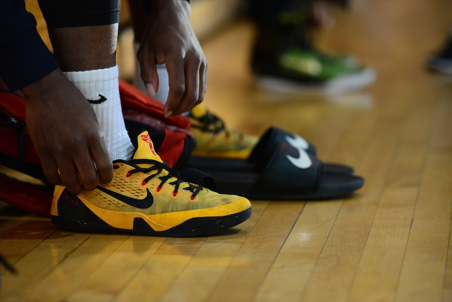 A competitor laces up his shoes to hit the court at the 3-on-3 basketball challenge at Osan Air Base, Republic of Korea, Sept. 29, 2015. The challenge was just one of the events that took place during the second annual Osan Cup.