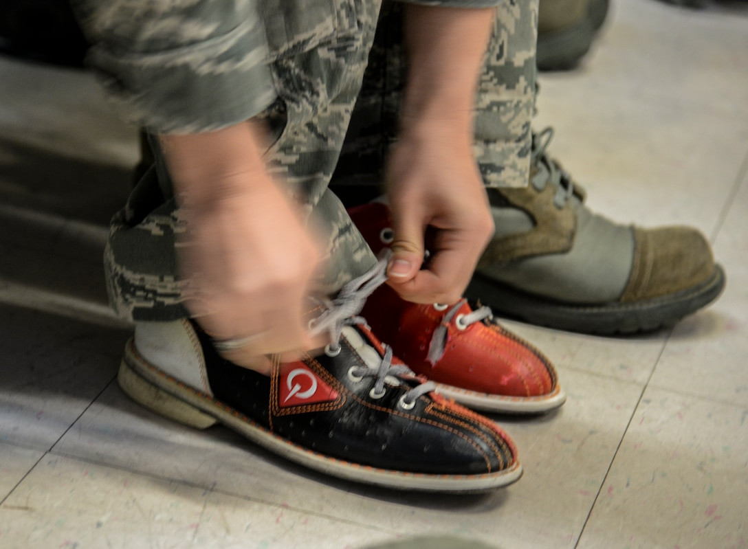 An Airman laces up her bowling shoes prior to her team's turn to start during a bowling tournament at the MiG Alleys Bowling Center during the Osan Cup at Osan Air Base, Republic of Korea, Sept. 30, 2015. The Osan cup is a sport-oriented, two-day event that puts squadrons and service members against each other in a battle royal to show who has the most skill, strength and knowledge. (U.S. Air Force photo/Tech. Sgt. Travis Edwards)