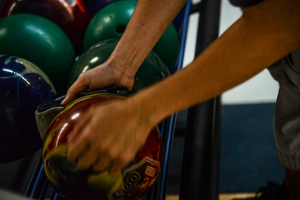 An Airman wipes down his ball before his game begins at the MiG Alleys Bowling Center during the bowling tournament in the Osan Cup at Osan Air Base, Republic of Korea, Sept. 30, 2015. The Osan cup is a sport-oriented, two-day event that puts squadrons and service members against each other in a battle royal to show who has the most skill, strength and knowledge. (U.S. Air Force photo/Tech. Sgt. Travis Edwards)