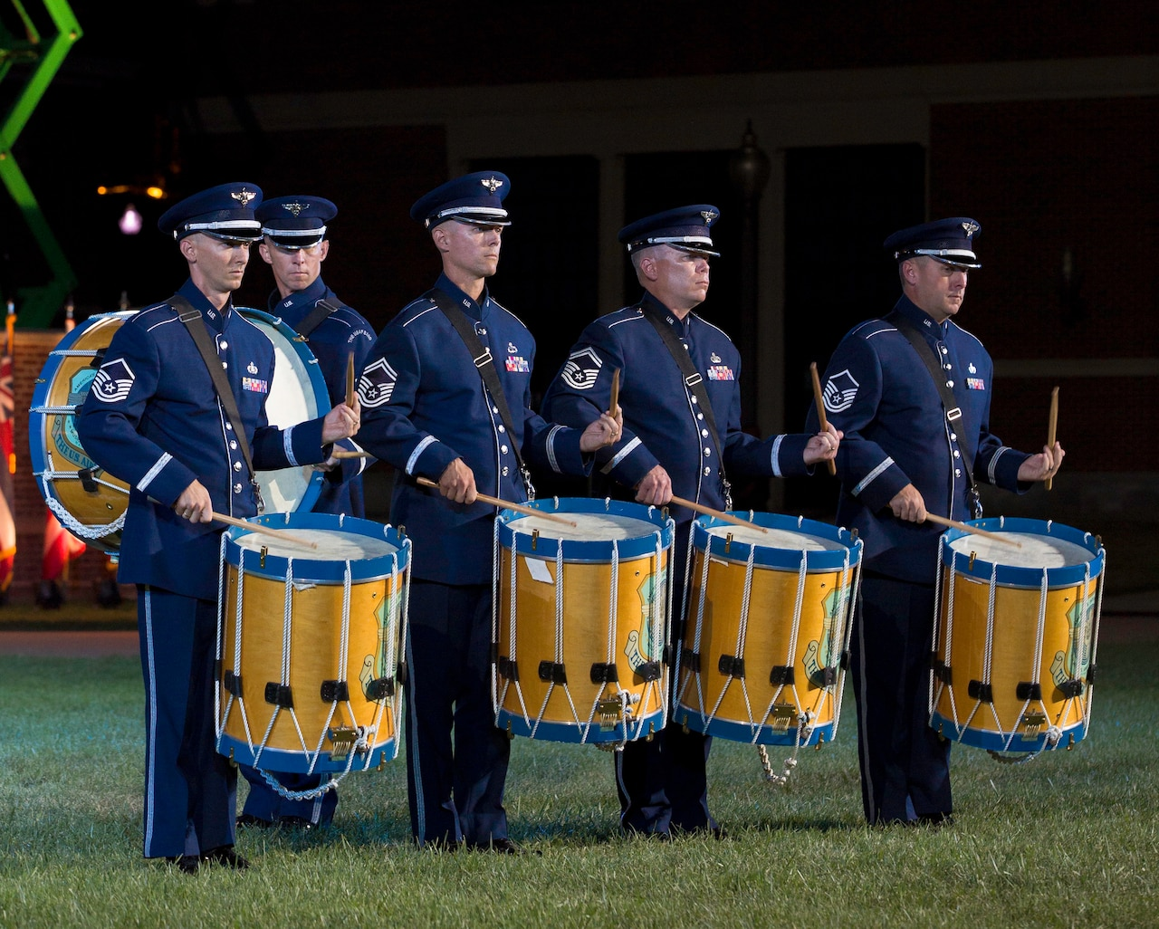 Four airmen in dress blue uniforms play large drums on a grassy field at night. A fifth airman walks past in the background.