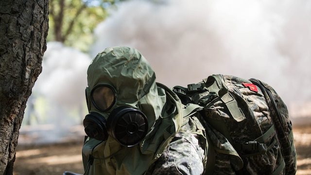 Republic of Korea Marine Lance Cpl. Jun Shin puts on his gas mask during a gas attack scenario as part of Korea Marine Exchange Program 15-12 at Gunha-Rhi, Republic of Korea, Sept. 17, 2015. The U.S. and ROK Marines practiced quickly putting on their gas mask and carrying the wounded to safety. KMEP 15-12 is an exercise in a series of continuous bilateral training exercises that enhance the ROK and U.S. alliance, promote stability on the Korean Peninsula and strengthen ROK and U.S. military capabilities and interoperability. Shin, from Ulsan, ROK, is with 2nd Company, 11th Battalion, 1st Regiment, 2nd Marine Division, ROK Headquarters Marine Corps.