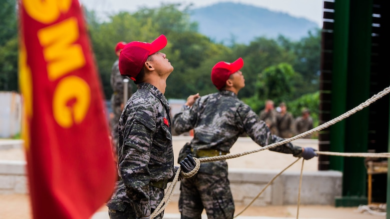Republic of Korea Marine ranger instructors act as belay men during a company competition among integrated teams of ROK and U.S. Marines during Korean Marine Exchange Program at Yooghuk Dae, Munseu San Mountain, Republic of Korea, Sept. 11, 2015. The U.S. and ROK Marines competed for the fastest company in rappelling, rock climbing and rope climbing before a sprint to the finish line. KMEP 15-12 is a bilateral training exercise that enhances the ROK and U.S. alliance, promotes stability on the Korean Peninsula and strengthens ROK and U.S. military capabilities and interoperability. The ROK Marines are with 11th Battalion, 1st Regiment, 2nd Marine Division, ROK Headquarters Marine Corps.