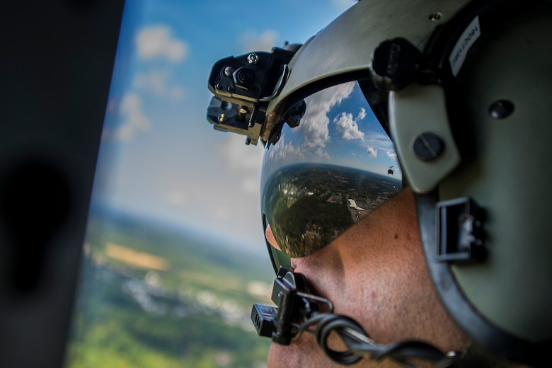 Tech. Sgt. Justin Cole, a 1st Helicopter Squadron flight engineer, looks back at a UH-1N Iroquois during a flyover for the 2015 Joint Base Andrews Air  Show Sept. 19, 2015. The  1st HS performed a fly-by for the crowd during the event. (U.S. Air Force photo/Airman 1st Class Ryan J. Sonnier)