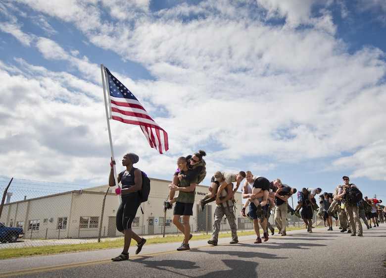 "Participants march past the vehicle maintenance facility carrying simulated wounded personnel Sept. 24, 2015, at the GoRuck team building challenge at Eglin Air Force Base, Fla. More than 45 participants pushed themselves through the physical scenarios led by a special forces veteran, to earn the blue and black ""GoRuck"" patch. (U.S. Air Force photo/Samuel King Jr.)"