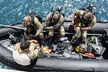 Airmen from the 320th Special Tactics Squadron at Kadena Air Base, Japan, ready their scuba diving gear during an amphibious operations exercise Sept. 22, 2015, off the west coast of Okinawa, Japan. Teamwork is vital to the successful and safe completion of special tactics objectives, especially in the face of adversities such as harsh weather conditions and terrain. (U.S. Air Force photo/Senior Airman John Linzmeier)