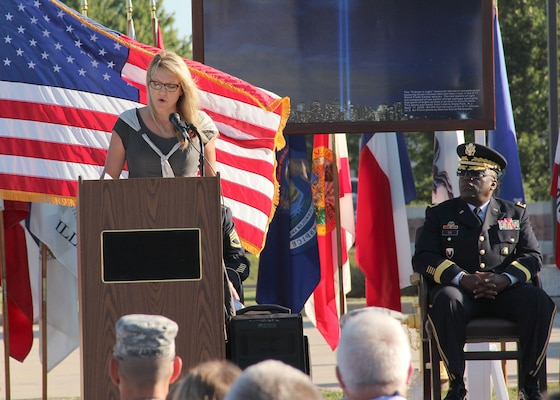 Brig. Gen. Richard B. Dix listens as Carmen Gordon, the Gold Star wife of Army Master Sgt. Gary Gordon, speaks of her husband's heroics and ultimate sacrifice during a Patriot Day and POW/MIA Remembrance Ceremony. (Photo by Sherre Mitten-Bell, DLA Distribution Susquehanna, Pa.)