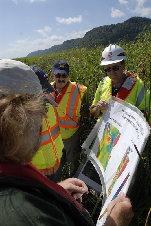 Members of the Wisconsin Department of Natural Resources and the U.S. Army Corps of Engineers look at aerial maps of the Mississippi River while conducting a tour to see the island creation process in action.