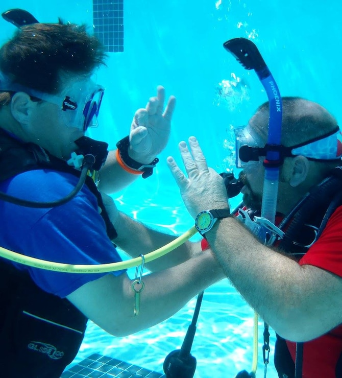 Students Michael Winkler and Tommy Kirklin signal to each other that they are OK as they practice buddy breathing – an emergency out-of-air procedure when scuba diving.