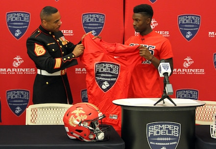 Staff Sgt. Curtis Rankin, a recruiter with Marine Corps Recruiting Substation Temecula, presents Demetric Felton with a jersey for the 2016 Semper Fidelis All-American Bowl at Great Oak High School in Temecula, Calif., Oct. 1. Felton is selected to play both a running back and a strong-side linebacker position for the West Coast team.