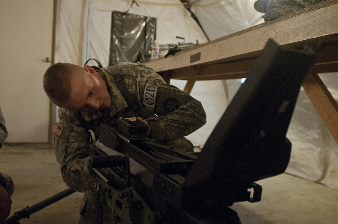 Spc. Mark Whaley, 1138th Engineer Company (Sapper), Missouri National Guard, disassembles a MK 19 grenade launcher during a weapons jumble at Sapper Stakes 2015 in Fort Chaffee, Ark., Aug. 30. Each team member was required to disassemble, reassemble and perform a weapons check on a weapon system. (U.S. Army photo by Staff Sgt. Debralee Best)