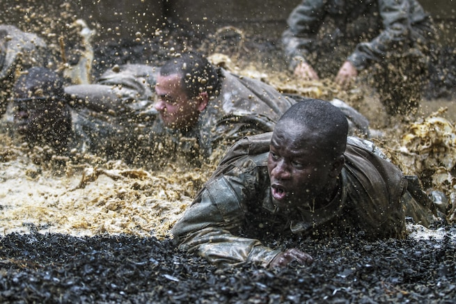 Soldiers in their second week of basic combat training low-crawl through a mud pit serving as the final obstacle of the Fit to Win endurance course on Fort Jackson, S.C., Oct. 1, 2015. The soldiers are with Company B, 3rd Battalion, 34th Infantry Regiment. U.S. Army photo by Sgt. 1st Class Brian Hamilton