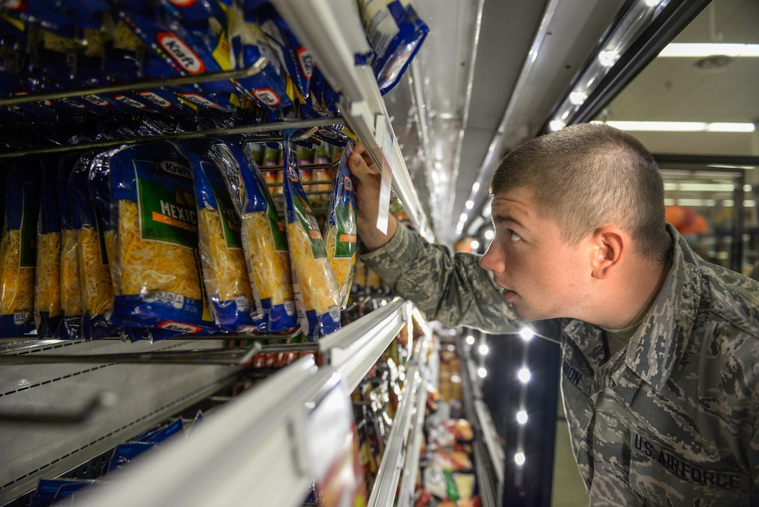 An Airman-in-Training restocks the shredded cheese section at the Defense Commissary Agency cooler shelves on Sheppard Air Force Base, Texas, Sept. 27, 2015.  More than 150 Airmen and volunteers helped rescue more than $200,000 in perishable grocery items from a lighting strike that shut down the commissary power. (U.S. Air Force photo/Tech. Sgt. Mike Meares)