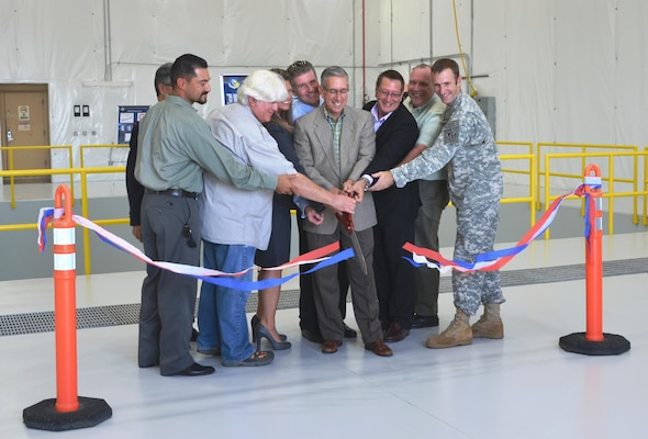 KIRTLAND AIR FORCE BASE, N.M. – Deputy District Commander Maj. Jason Melchior (far right) and District Project Manager Filemon Gallegos (far left) help cut the ribbon officially opening the Building 903 Lab Space, Sept. 23, 2015.