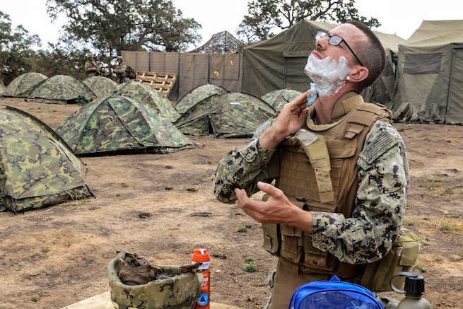 Navy Petty Officer 3rd Class Michael Whisenhunt shaves during a field training exercise on Fort Hunter Liggett, Calif., Sept. 28, 2015. Whisenhunt, a construction electrician, is assigned to Naval Mobile Construction Battalion 4. The exercise tests the battalion's ability to enter hostile locations, build assigned construction projects and defend against enemy attacks, using realistic scenarios. U.S. Navy photo by Petty Officer 1st Class Rosalie Chang