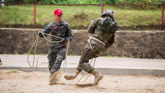 U.S. Marine Cpl. Carlson, right, dismounts the rappel rope during a company competition for Korean Marine Exchange Program 15-12 at Yooghuk Dae, Munseu San Mountain, Republic of Korea, Sept. 11, 2015. The U.S. and ROK Marines participated in a race of the fastest company to complete rappelling, rock climbing and rope climbing before a sprint to the finish line. KMEP 15-12 is a bilateral training exercise that enhances the ROK and U.S. alliance, promotes stability on the Korean Peninsula and strengthens ROK and U.S. military capabilities and interoperability. Carlson, from Virginia Beach, Virginia, is a rifleman with Fox Company, 2nd Battalion, 3rd Marine Division and attached through the Unit Deployment Program to III Marine Expeditionary Force. The ROK Marines are with 11th Battalion, 1st Regiment, 2nd Marine Division, ROK Headquarters Marine Corps.