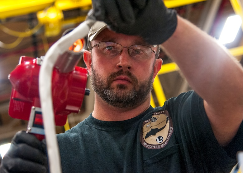 "Travis Penfold, M1 Support Services aircraft mechanic for the 37th Helicopter Squadron , shrink wraps a protective casing on a starter generator's wires Oct. 2, 2015, in the 37th HS hangar on F.E. Warren Air Force Base, Wyo. The work is part of ""phase maintenance,"" which is scheduled upkeep for UH-1N ""Huey"" Bell Helicopters performed after a certain number of flight hours. (U.S. Air Force photo by Senior Airman Jason Wiese)"