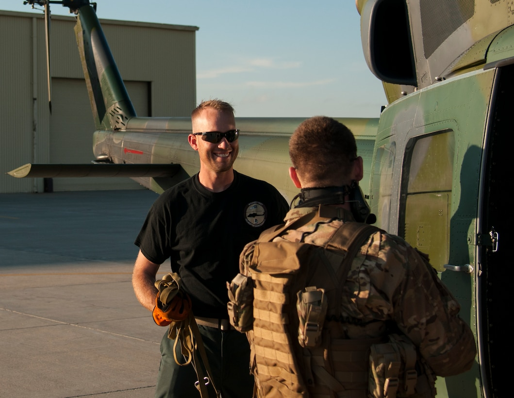 """Ben Postma, M1 Support Services aircraft mechanic, talks with a 790th Missile Security Forces Squadron Tactical Response Force Airman on F.E. Warren Air Force Base, Wyo., June 12, 2015. The defender just returned from the 90th Missile Wing Missile Complex on the UH-1N """"Huey"""" Bell Helicopter that Postma was preparing to inspect. (U.S. Air Force photo by Senior Airman Jason Wiese)"""
