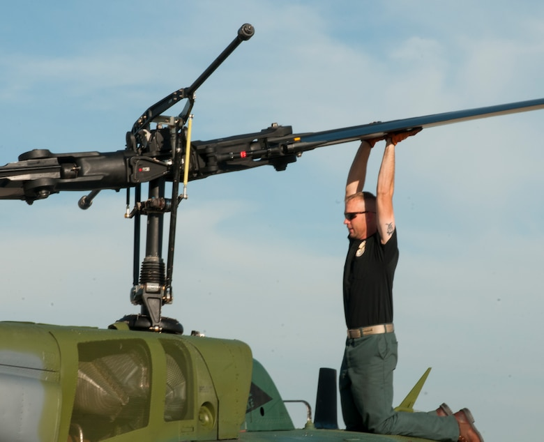 "Ben Postma, M1 Support Services aircraft mechanic, lifts a propeller blade of a UH-1N ""Huey"" Bell Helicopter on F.E. Warren Air Force Base, Wyo., June 12, 2015. Lifting one blade lowers the other so it can be reached from the ground and tied to the body of the helicopter, preventing it from spinning freely during maintenance. (U.S. Air Force photo by Senior Airman Jason Wiese)"
