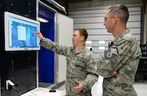 U.S. Air Force Senior Airman Sean Kirby, a 354th Civil Engineer Squadron emergency management journeyman, explains joint effects modeling to Master Sgt. Jason Blair, the 354th CES emergency management superintendent, Sep. 29, 2015, at Eielson Air Force Base, Alaska. The model on the screen shows a simulated chlorine plume and what areas could be affected. (U.S. Air Force photo by Airman 1st Class Cassandra Whitman/Released)