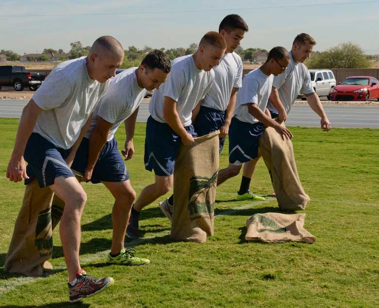 Airmen use teamwork to complete a potato sack race during Wingman Day 2015 at Luke Air Force Base, Sep. 20, 2015. The potato sack race was one of multiple challenges presented during the team-based obstacle course setup as part of the events of the day. (U.S. Air Force photo by Airman 1st Class Ridge Shan)