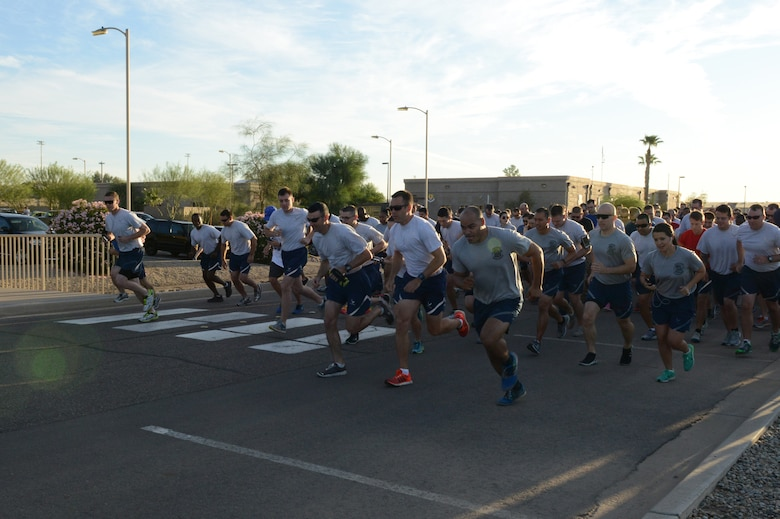 Luke Airmen participate in a 5K fun run at the start of Wingman Day at Luke Air Force Base, Arizona, Sept. 30, 2015. Wingman Day is a day for Airmen to compete and strengthen the bond between squadrons. (U.S. Air Force photo by Senior Airman James Hensley)