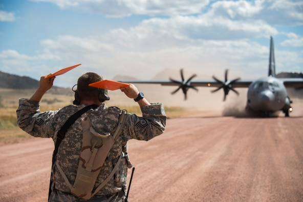 Tech Sgt. Ryan Padgett, a ramp coordinator for the 821st Contingency response Squadron from Travis Air Force Base, Calif., marshals in a C-130 Aircraft into parking area at Red Devil Landing Zone, Colo., on September 14, 2015. Approximately 150 Airmen from the 821st Contingency Response Group at Travis Air Force Base, Calif., participated in a first-of-its-kind Joint contingency response exercise from Sept. 8-19 at five locations (Southern California Logistics Airfield, Calif., Freedom Landing Zone, Calif., Gunnison Region Airfield, Colo., Red Devil Landing Zone, Colo., Peterson Air Force Base, Colo., and Fort Carson, Colo.). During the training, 821st CRG Airmen supported more than 275 Soldiers from Fort Carson, Colo., during air drop missions, helicopter training, coordinated Apache air support, and personnel and equipment airlift training. The Contingency Response (CR) training was constructed to primarily develop unique CR-oriented training objectives to improve down range effectiveness in preparation for real-world responses. (U.S. Air Force Photos by Tech. Sgt. Matthew Hannen)