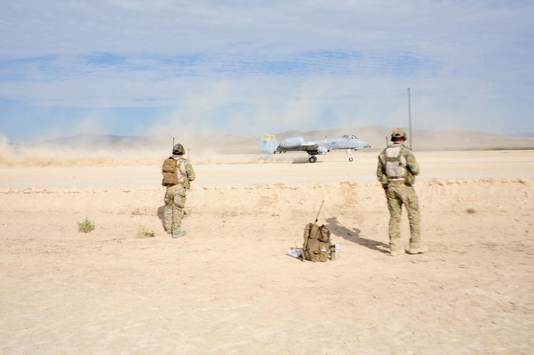 Two U.S. Air Force combat controllers from the 22nd Special Tactics Squadron observe an A-10C Thunderbolt II taking off during austere landing training on Bicycle Lake Army Airfield at the National Training Center range, Fort Irwin, Calif., Sept. 22, 2015. Combat controller's survey and establish airfields in austere or hostile areas while also providing air traffic control to land aircraft during combat and humanitarian missions. (U.S. Air Force photo by Senior Airman Betty R. Chevalier/Released)