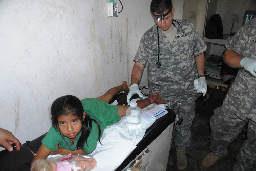 QUEBRADA NEGRA, Panama – Sgt. Rob A. Slaughter, medical provider from Joint Task-Force Bravo's Medical Element, treats the burn wound of a young girl in Quebrada Negra, Panama, September 23, 2015 during a medical readiness training exercise between Joint Task Force-Bravo and the Panamanian Ministry of Health. The U.S. and Panamanian medical providers were able to reach out to the Colorado Pediatric Burn Center in order to provide a joint consultation and explain proper care for the burn. (U.S. Army photo by Sgt. Tia Sokimson)