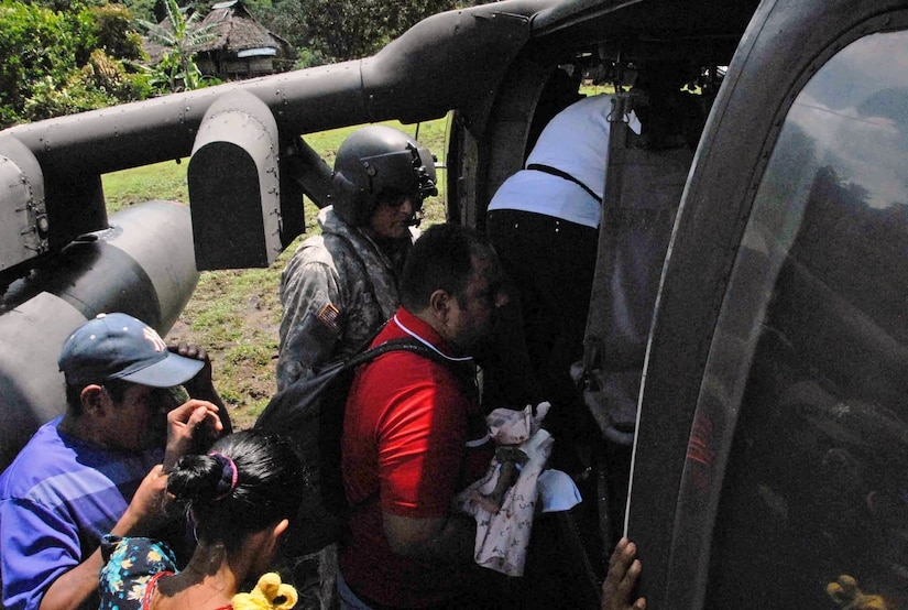 CORONTE, Panama – Victor Luis Pineda, a 30-day-old child, is loaded onto a from Joint Task Force-Bravo helicopter by a representative from the Panamanian Ministry of Health, accompanied by his mother in Coronte, Panama, September 25, 2015, in order to be transported to the Ramballa Air Field, to receive life-saving treatment. Exercises such as these validate medical expeditionary capabilities, enhance readiness and foster partner nation response and capacity. (U.S. Army photo by Sgt. Tia Sokimson)