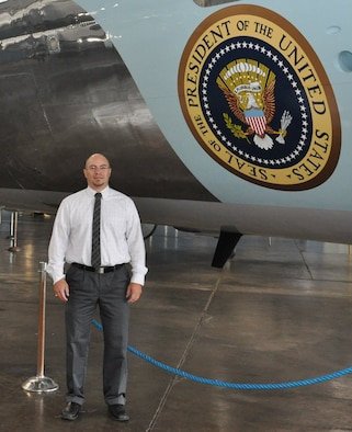 Edgardo Santiago-Maldonado stands in front of a former presidential aircraft located at the National Museum of the United States Air Force. (U.S. Air Force photo/Bryan Ripple)