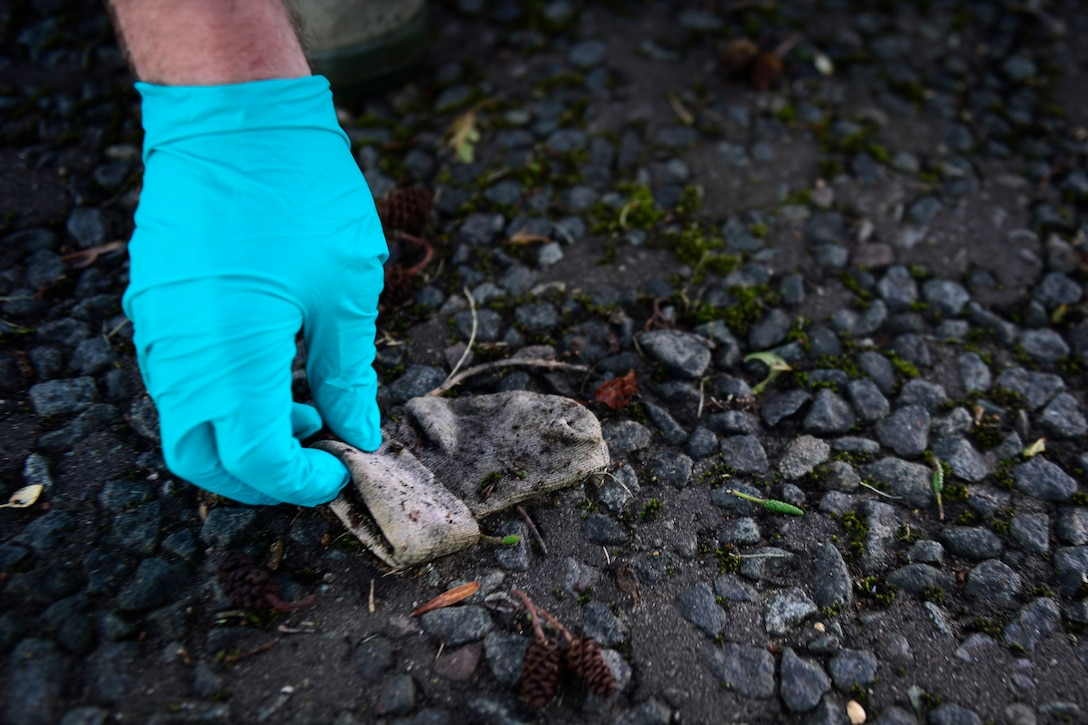 A Liberty Airman picks up trash during a Base Clean-up event at Royal Air Force Lakenheath, England, Sept. 25, 2015. Keeping the base clean also removes debris that could potential result in foreign object damage incidents. (U.S. Air Force photo by Airman 1st Class Erin R. Babis/Released)