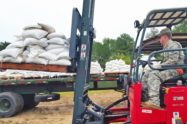 U.S. Army Spc. Joshua Monk helps move and deliver sandbags to county emergency managers during flood response in Chesterfield, S.C., Oct. 3, 2015. Monk is a forklift operator with the 1052nd Transportation Company, South Carolina National Guard. State officials projected historic amounts of rainfall for the region after a weather system collided with the outer bands of Hurricane Joaquin off the coast. South Carolina National Guard photo by Sgt. David Erskine