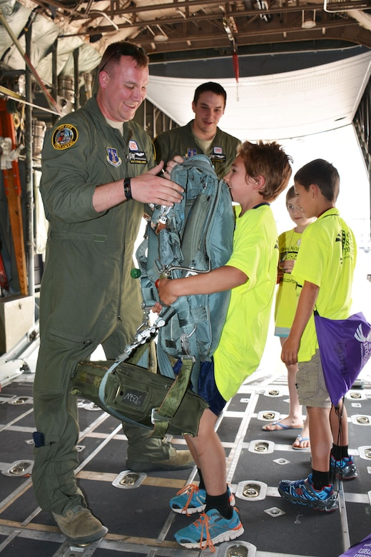 Montana Air National Guard C-130 Hercules Loadmaster Master Sgt. Steven Jager helps a young family member of a Montana National Guardsman feel the weight of a parachute during a tour of the transport aircraft. Eleven children of Guard families were participating in Kids Mobility Day at the 120th Airlift Wing in Great Falls, Mont., Aug. 20, 2015. (U.S. Air National Guard photo/Senior Master Sgt. Eric Peterson)