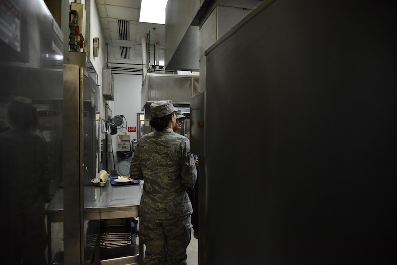 Senior Airman Leah Smith, 379th Expeditionary Medical Operations Support Squadron Bioenvironmental, walks through the kitchen of a dining facility inspecting the ventilation systems September 30, 2015 at Al Udeid Air Base, Qatar. (U.S. Air Force photo/Staff Sgt. Alexandre Montes)