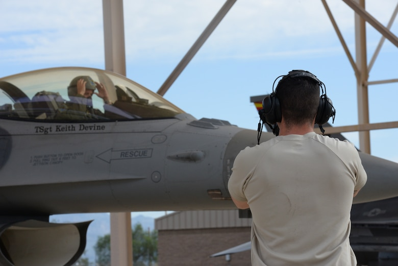 A crew chief ensures an F-16 pilot from the Aerospace Control Alert Detachment from the 162nd Wing is prepared for take-off Sept. 12, 2015, at Davis-Monthan Air Force Base. It is the responsibility of a crew chief from the Aerospace Control Alert Detachment to perform the final checks before a pilot takes flight. The detachment maintains the ability to quickly scramble in response to airborne threats in the Southwest United States, as well as proactively defend large gatherings and high profile events. (Air National Guard photo by Senior Airman Jackson Hurd)